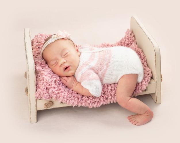 Kleine baby in gebreide romper op babybed