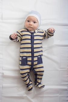 Kleine baby in kleding met een grappig gezicht op wit vel.