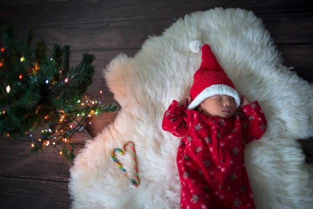 Kleine baby in rode dop van de kerstman viert kerstmis