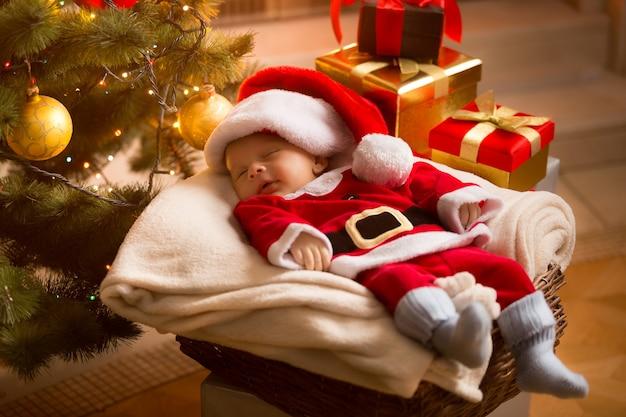 Kleine baby kerstman slapen onder de kerstboom met cadeautjes
