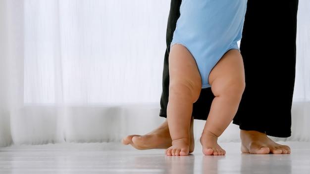 Kleine baby leert lopen met steun en zorg van de moeder.