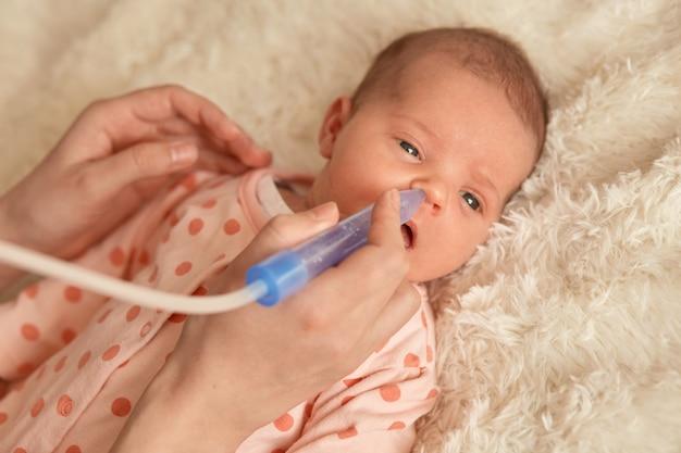 Kleine baby liggend op bed op zachte deken, anonieme moeder met nasale aspiratie om voor haar pasgeboren kind te zorgen. kind met haar moeder, kind met slaper met stippen.