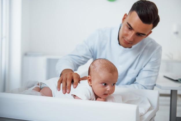 Kleine baby liggend op de tafel. de jonge kinderarts is overdag in de kliniek.