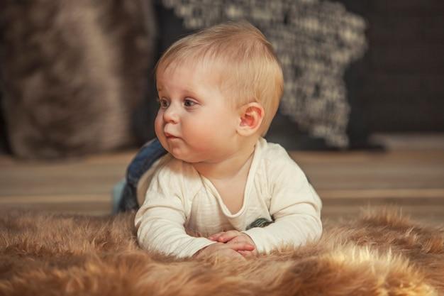 Kleine baby liggend op een bontdeken thuis close-up portret