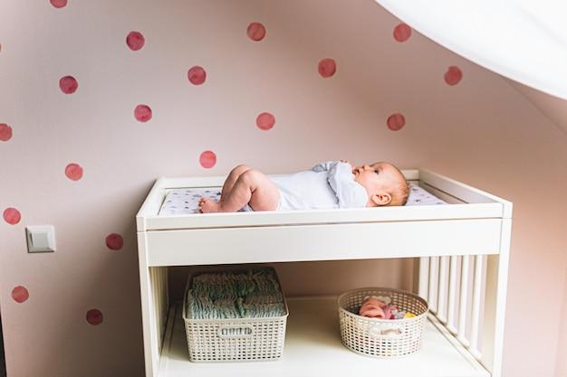 Kleine baby ligt op de tafel van de kinderen in de buurt van raam. er is een pasgeboren kind op de baby commode.