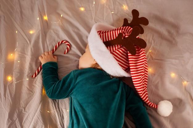 Kleine baby ligt op het bed in een kerstkostuum en een hoed met hertengewei. kerstmis en nieuwjaar.