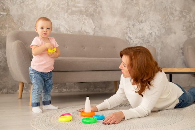 Kleine baby meisje verzamelt een piramide met grootouders in de woonkamer. grootmoeder speelt met kleindochter op de vloer