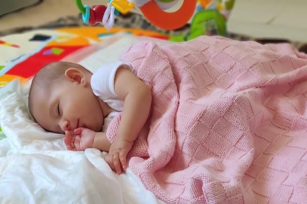 Kleine baby slaapt in bed liggend op de zijkant bedekt met een roze deken