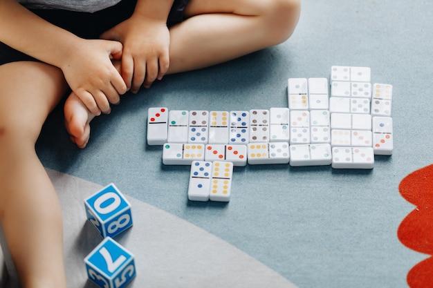 Kleine baby speelt dominostenen in zijn kamer op de vloer