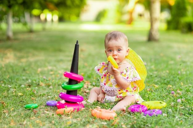 Kleine baby speelt in de zomer met een piramide op het groene gras