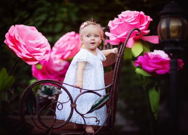 Kleine baby staande op een tuinbank onder grote roze rozen