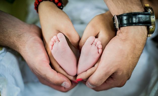 Kleine baby voet in handen van de ouders