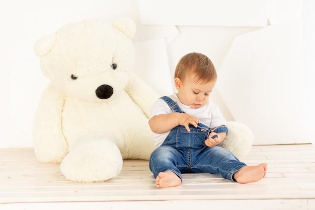 Kleine baby zes maanden oud in spijkerbroek thuis spelen in de buurt van een grote teddybeer