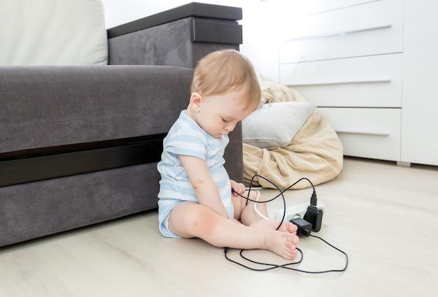 Kleine baby zit alleen in de woonkamer en speelt met elektrische kabels