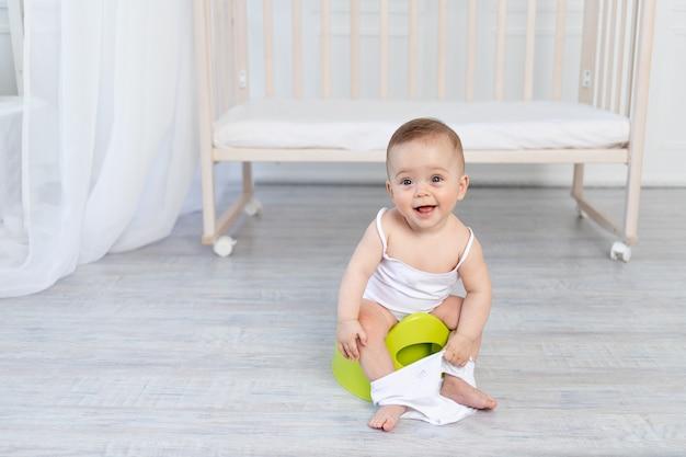 Kleine baby zittend op een potje, babytoilet