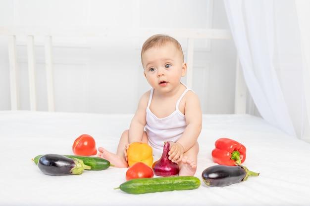 Kleine baby zittend op het bed in de kinderkamer met groenten, babyvoeding concept,