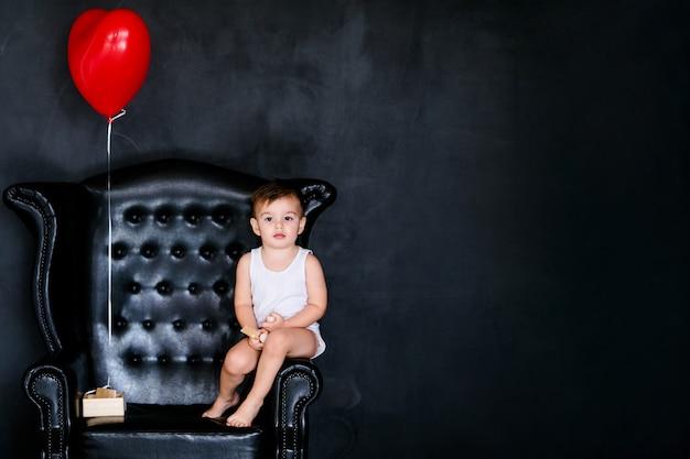 Kleine babyjongen 2 jaar oud in het witte t-shirt zittend op de fauteuil met rode hartballon