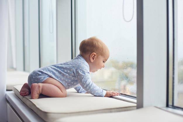 Kleine babyjongen crawlibg in de buurt van groot raam