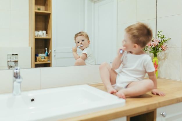 Kleine babyjongen leert zijn tanden poetsen in de badkamer