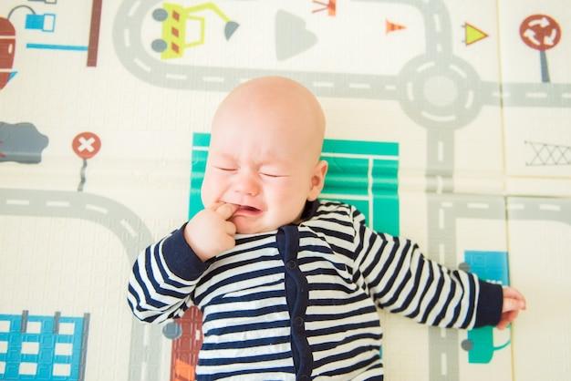 Kleine babyjongen liegt en huilt. bovenaanzicht