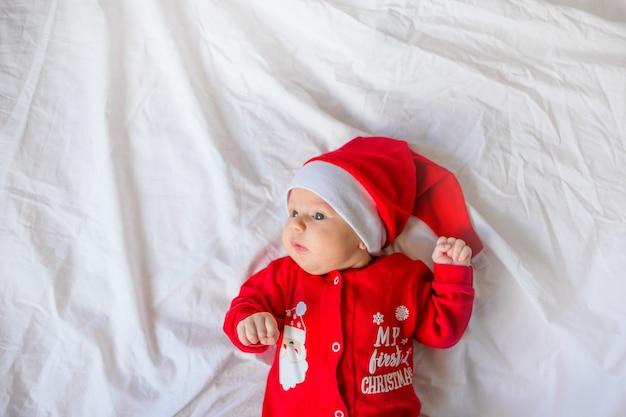 Kleine babyjongen liggend op wit linnen in de kerstmuts
