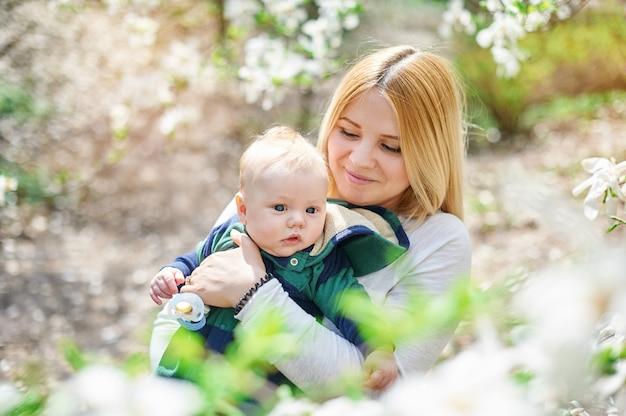Kleine babyjongen met haar jonge moeder in de bloeiende lente tuin
