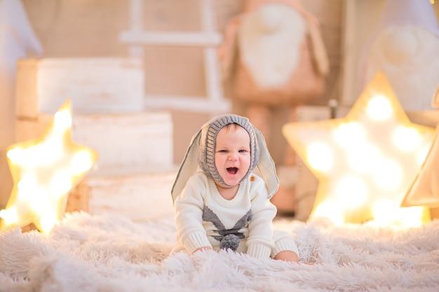 Kleine babyjongen poseren in een witte kamer met kerst achtergrond