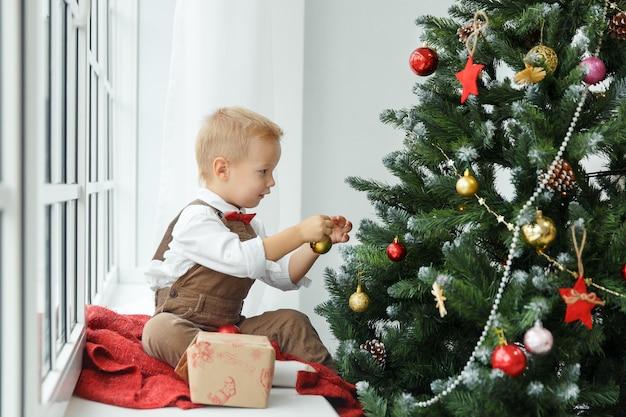 Kleine babyjongen versieren een kerstboom speelgoed. vakantie, cadeau en nieuwjaarsconcept.