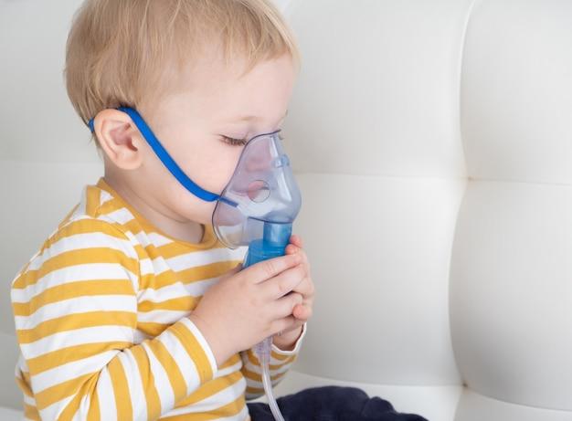 Kleine babyjongen zelf met behulp van stoominhalator vernevelaar masker zichzelf op het bed. kopieer ruimte.