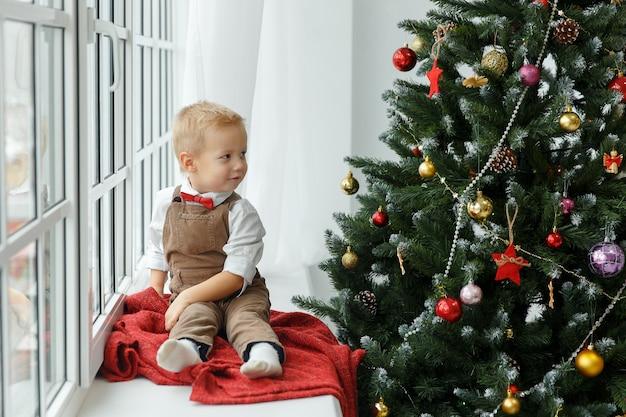 Kleine babyjongen zit bij het raam en kijkt op de kerstboom. feestdagen, cadeau en nieuwjaarsconcept