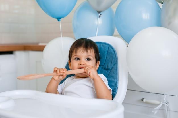 Kleine babyjongen zit in blauwe hoge stoel thuis