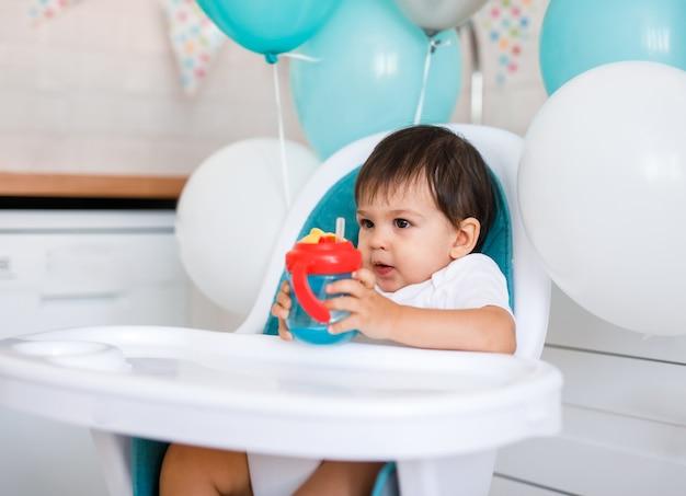 Kleine babyjongen zittend in blauwe kinderstoel thuis op witte keuken en drinkwater uit sippy cup op achtergrond met ballonnen.
