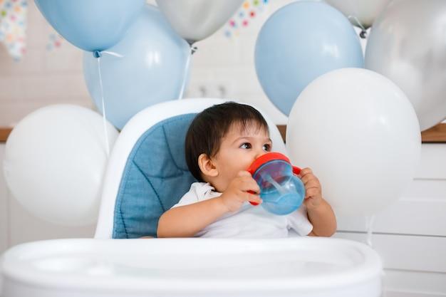 Kleine babyjongen zittend in blauwe kinderstoel thuis op witte keuken en spelen met houten grote lepel
