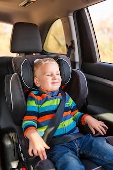 Kleine babyjongen zittend op een autostoeltje vastgemaakt in de auto.