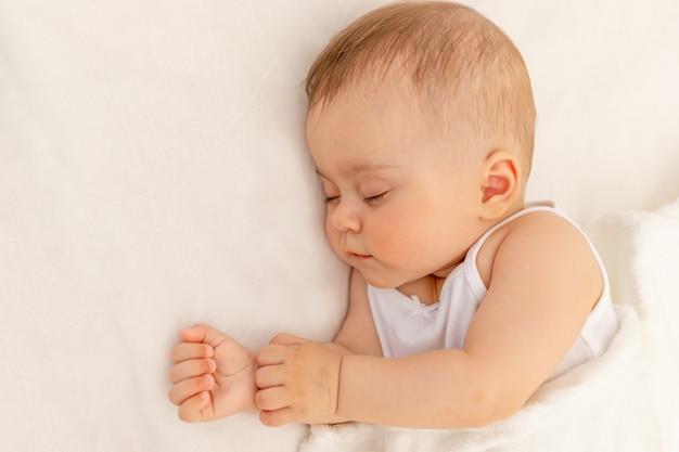 Kleine babymeisje slapen in een wit bed, gezonde babyslaap