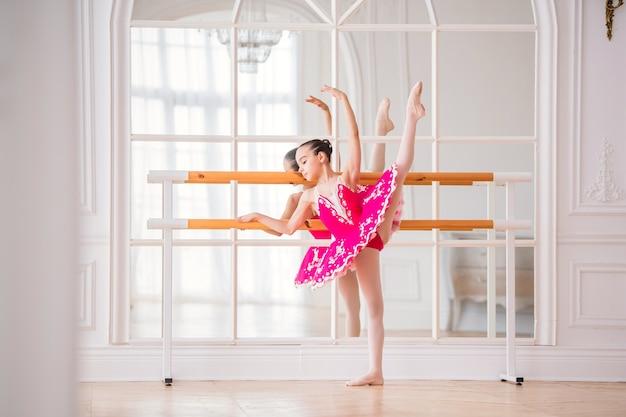 Kleine ballerina in een felroze tutu houdt zich bezig met een balletstaaf voor een spiegel in een mooie witte grote zaal