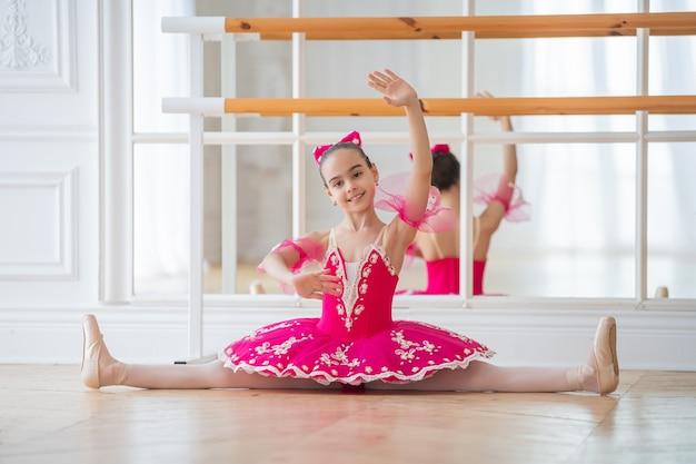 Kleine ballerina in helder roze tutu en pointes met strik op haar hoofd zit in mooie witte zaal