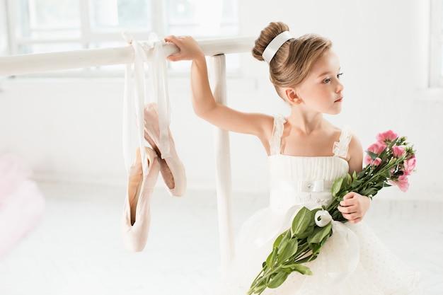 Kleine ballerina meisje in een tutu. aanbiddelijk kind dat klassiek ballet in een witte studio danst.