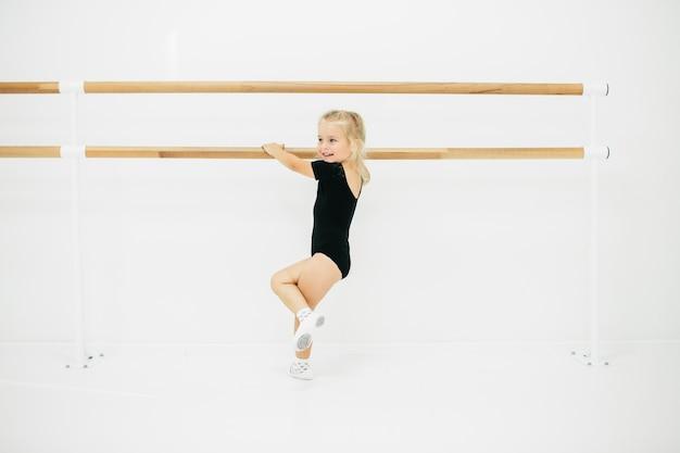 Kleine ballerina meisje in het zwart. schattig kind klassiek ballet dansen. kinderen dansen. kinderen optreden. jonge begaafde danser in een klas. preschool kind kunst lessen nemen.