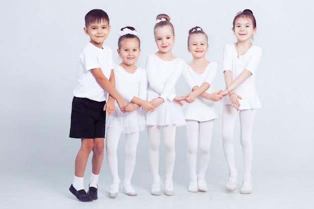Kleine ballerina's en jongen ballerun doen oefeningen en zitten op de vloer in witte balletles.