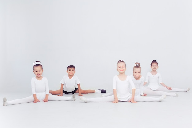 Kleine ballerina's meisjes en jongen doen splitsingen op witte vloer kopieerruimte