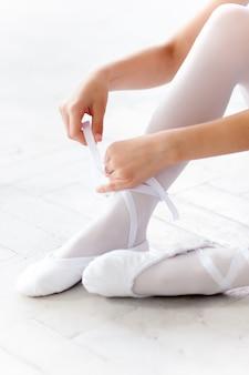 Kleine ballerina zittend op de vloer en te voet pointe-schoenen op witte ballet studio achtergrond zetten