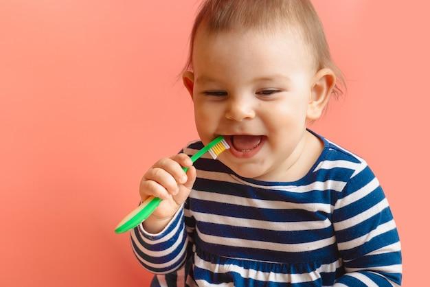 Kleine beautifulbaby-peuter schoonmakende tanden met kindborstel op roze achtergrond