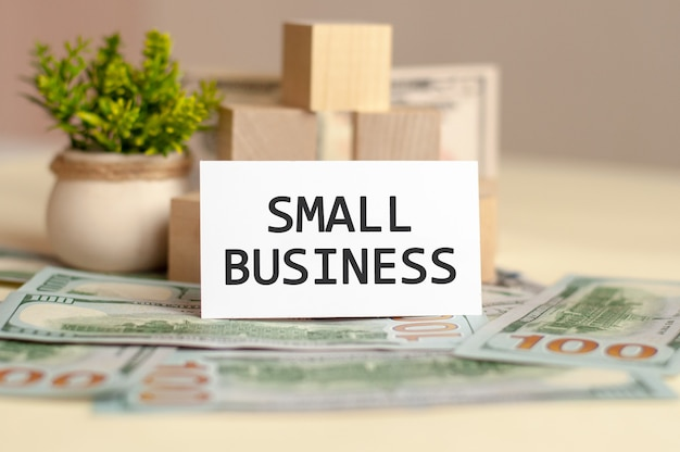 Kleine bedrijfstekst op wit papier, op de van geldrekeningen, bankbiljetten en houten blokken, bedrijfsconcept