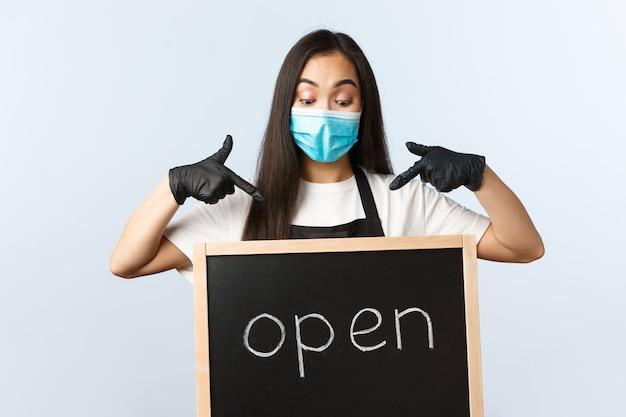 Kleine bedrijven, covid-19 pandemie, preventie van virus en werknemersconcept. opgewonden schattige aziatische vrouwelijke barista, café of winkelmedewerker met medisch masker wijzend naar we zijn open teken.