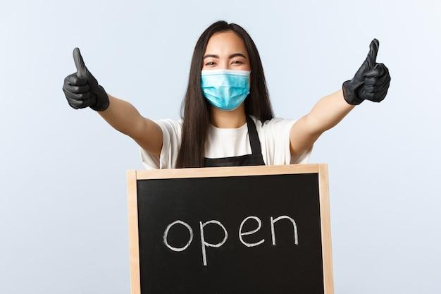 Kleine bedrijven, covid-19 pandemie, preventie van virus en werknemersconcept. vrolijke aziatische vrouwelijke winkelmedewerker, cafépersoneel met medisch masker nodigt bezoekers uit, duim omhoog en we zijn open teken