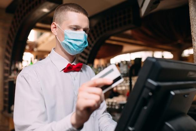 Kleine bedrijven, mensen en service concept. man of ober in medische masker aan balie met kassa werken bij bar of coffeeshop.