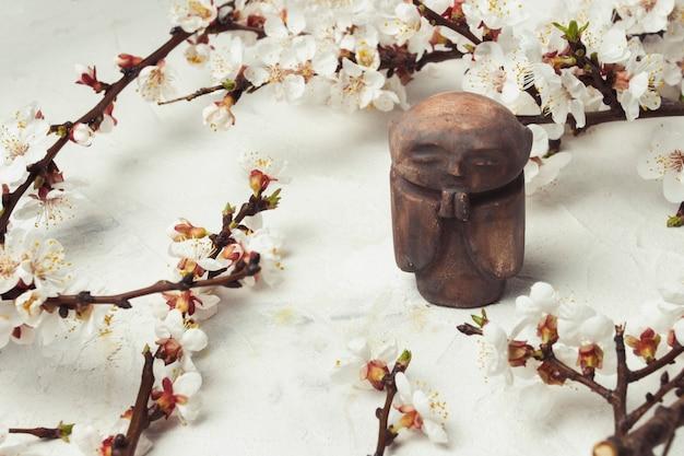 Kleine beeldje boeddhistische monnik en een takje kersenbloemen op een lichte stenen achtergrond.