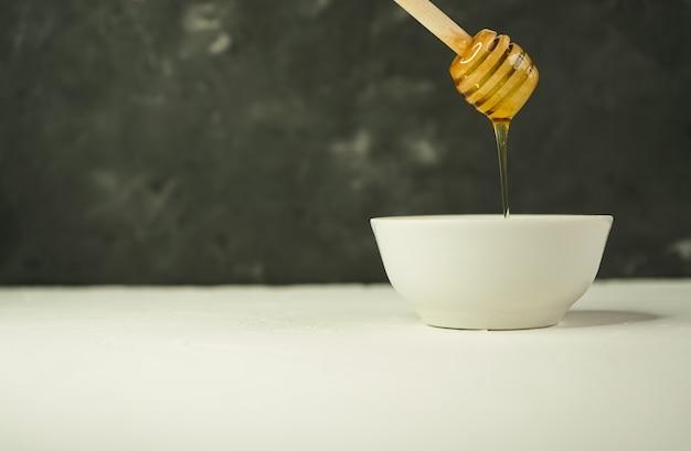 Kleine beker met natuurlijke honing en lepel