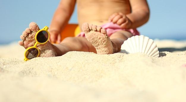 Kleine benen van een kind op het zand op het strand